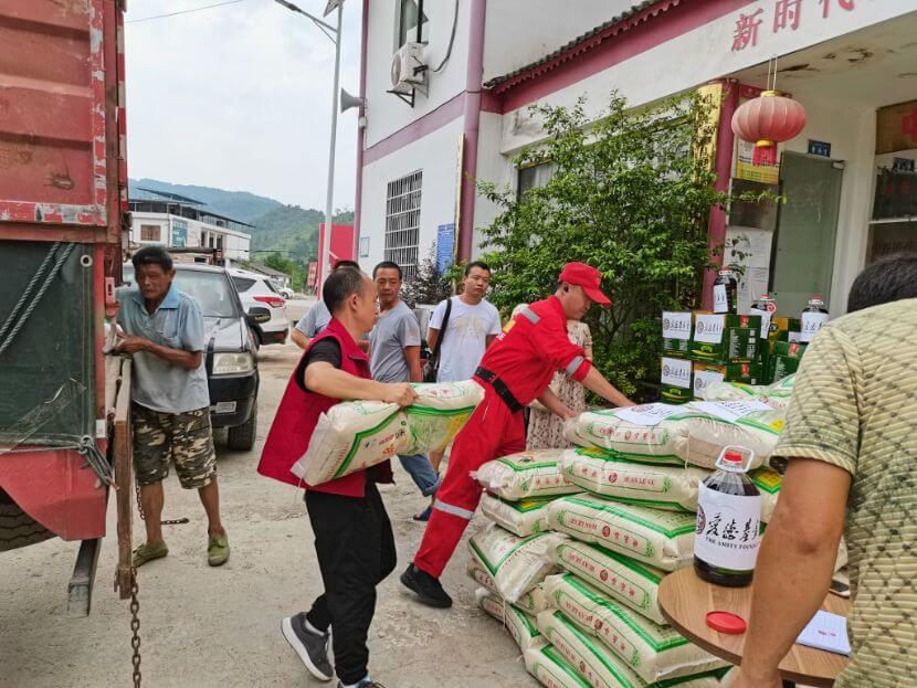 Amity staff and volunteers are unloading rice packages from a truck