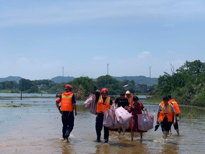 Volunteers carrying relief goods through a flooded area