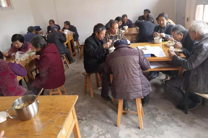 Elderly villagers eating together in an Amity sponsored canteen