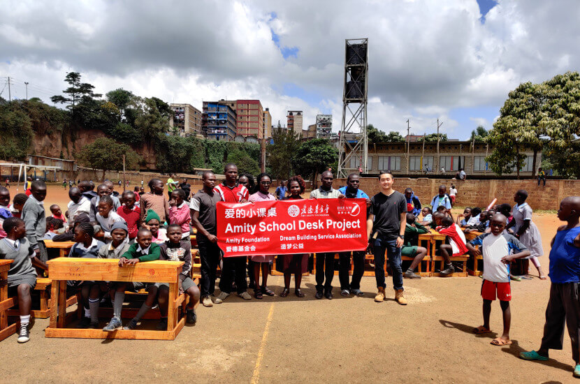 Group photo with local NGO staff and students working and benefiting at the Amity School Desk Project