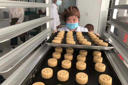 Staff of the Amity Bakery with trays of mooncakes