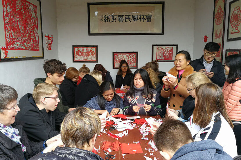 Overseas volunteers doing traditional Chinese papercuts in a village in China