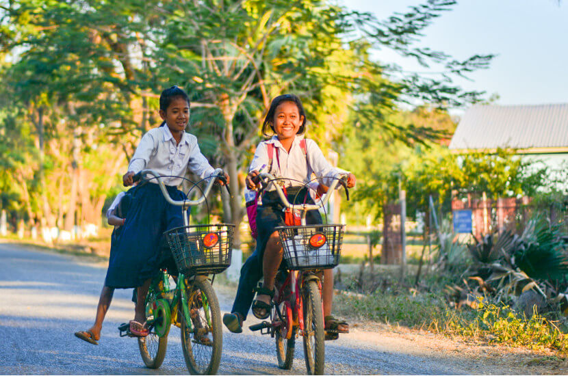 Cambodian students riding to their school which is supported by Amity