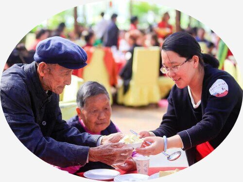 A volunteer giving food to an elderly couple