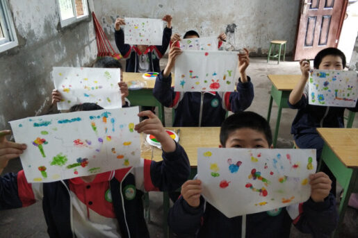 Children showing their paintings into the camera