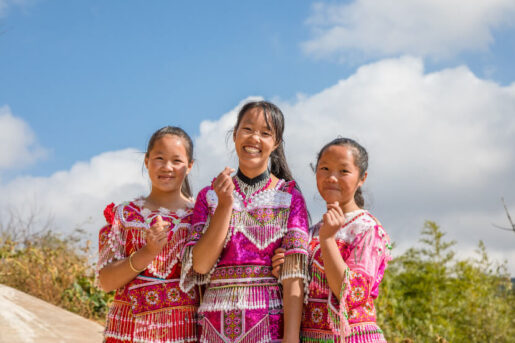 Three happy girls in traditional clothing showing hearts