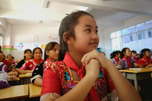 By the program supported girl in local traditional Miao clothes in a classroom