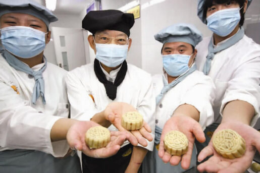Amity Bakery staff holding their freshly made mooncakes into the camera