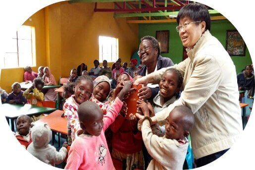 Mr Qiu surrounded by happy young students in Africa