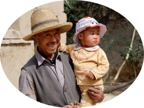 A farmer who benfited from Amity's rural development program with his grandkid in his arm