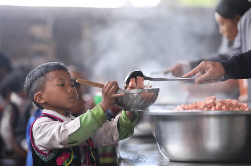 Young tudent recives lunch in mountainous areas under