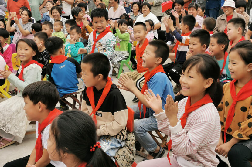 Children clapping during a community event performance