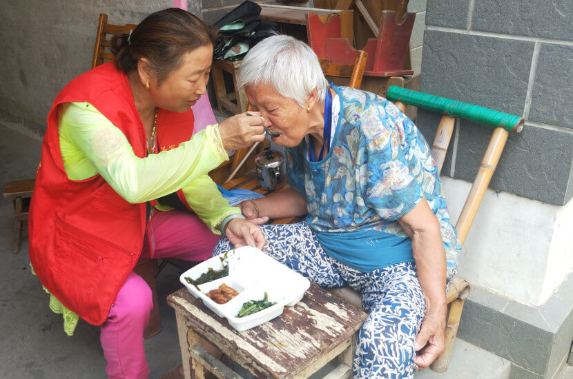 Volunteer assisting an elderly with having a meal