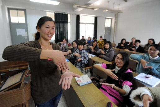 A female teacher is teaching sign language to students