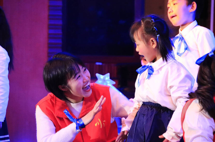 A volunteer interacting with a young girl during a performance of the