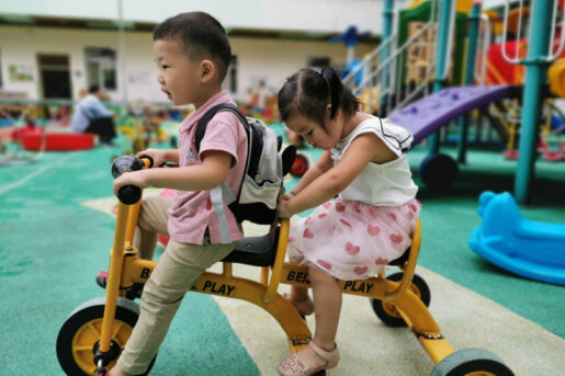 A young deaf boy and a girl riding a tandem bicycle at Amity's integration program
