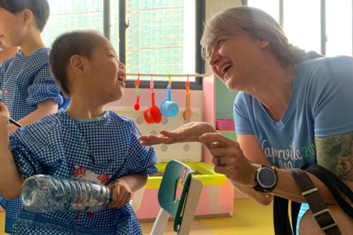An overseas care expert playing with a kid at the Amity children development center