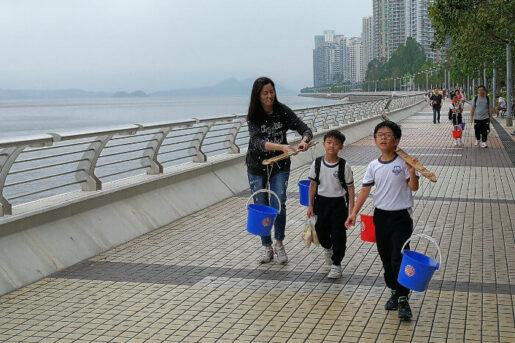 Students carrying buckets along a promenade in Hong Kong