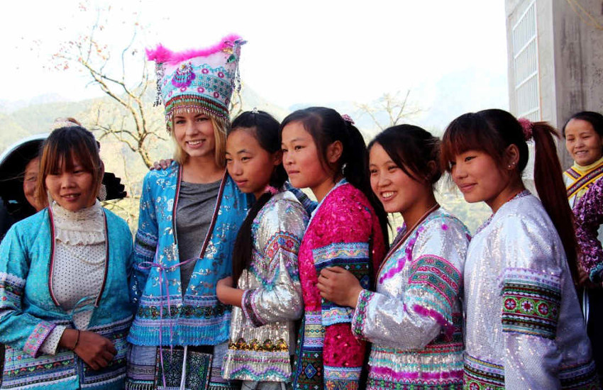 Amity volunteer from Norway taking photo with Chinese girls in traditional clothing