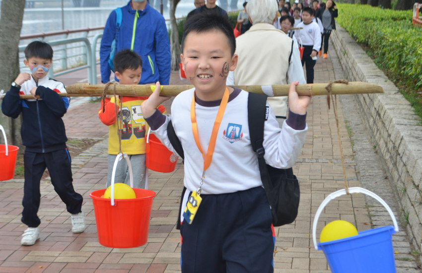 A student is carrying water buckets during the Walk for Living Water event