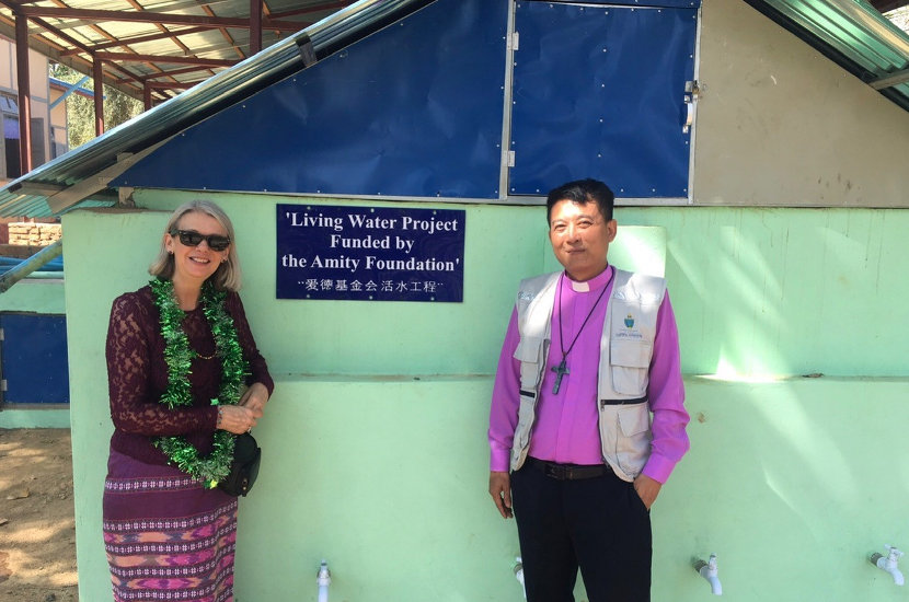 Debbie and the Bishop of Diocese of Toungoo standing in front of the new sanitation facilities built by Amity's water program