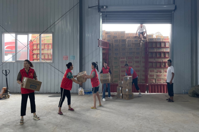Volunteer loading relief supplies out of a transit depot
