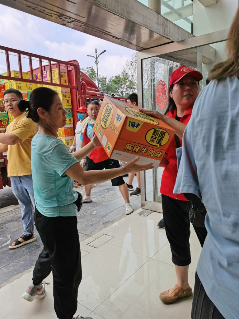 Volunteers unloading relief packages from a truck
