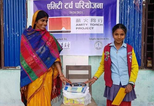 Torch project supplies are given out to a women and her daughter in Nepal