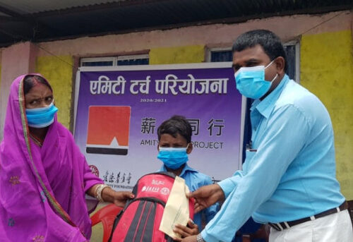 Torch project supplies are given out to a women and her son in Nepal