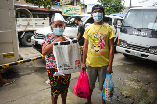 Elderly women and men carrying Amity and NCCP bags with supplies of the Torch project