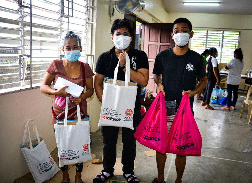 Elderly women and two men holding ACT Alliance/Amity/NCCP bags with Torch Program supplies