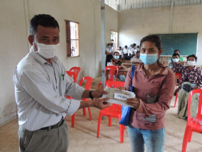 Cambodian local partner hands over cash incentives to mother of a student