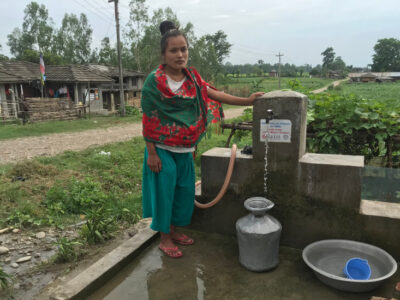 Village women in Myanmar stands next to a newly constructed water tap